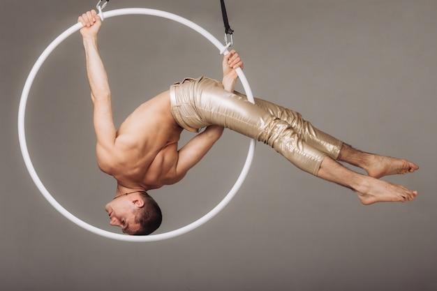 Męski gimnastyk powietrzny wykonuje akrobatyczny element na ringu