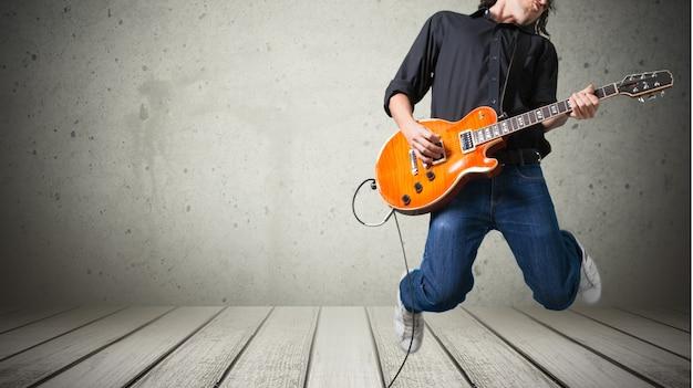 Męski gitarzysta grający muzykę na szarym tle ściany