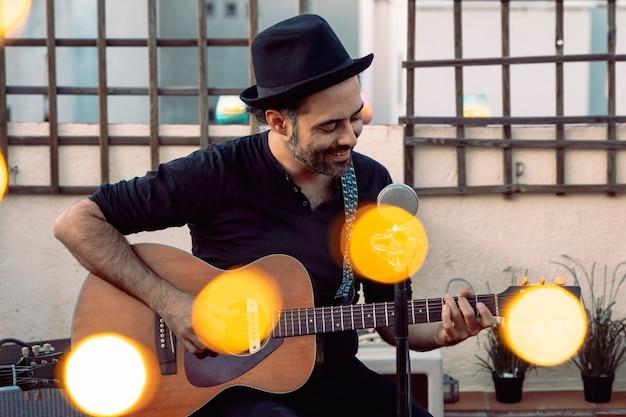 Męski gitarzysta wykonuje na dachu przy wiosna sezonem