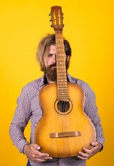 Męski gitarzysta z instrumentem muzycznym. koncepcja muzyki country. brodaty mężczyzna gra na gitarze akustycznej. przypadkowy facet wyraża ludzkie emocje. hipster z długimi włosami i wąsami gitarzysta. zmysłowe życie.