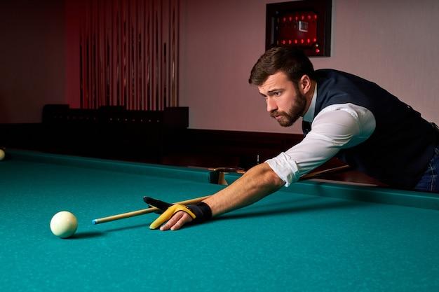 Męski gracz bilardowy znajdujący najlepsze rozwiązanie i kąt prosty w grze sportowej w bilard lub snooker, profesjonalny gracz bilardowy jest skoncentrowany