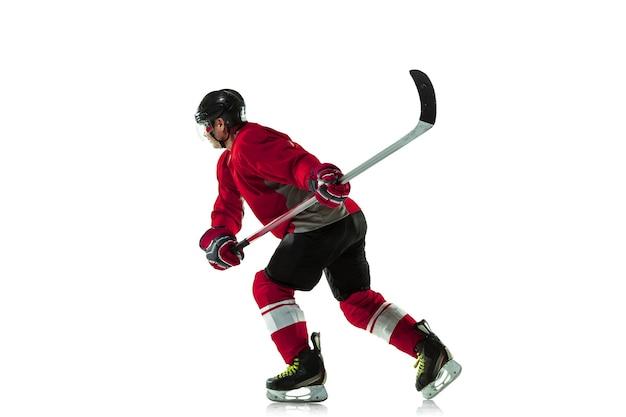 Męski gracz w hokeja z kijem na boisku i białej ścianie