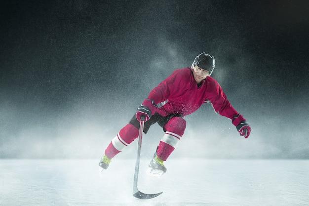 Męski gracz w hokeja z kijem na boisku i ciemnej ścianie