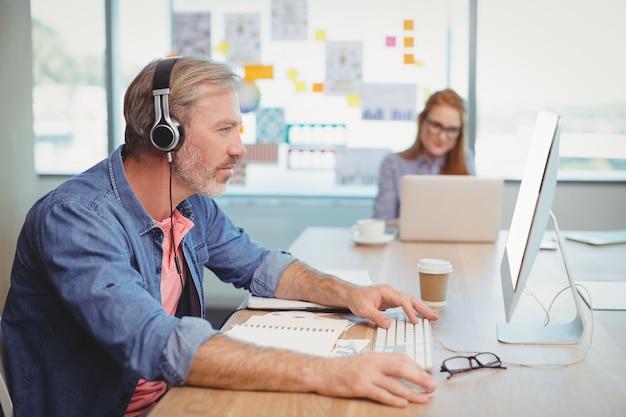 Męski grafik pracujący podczas słuchania muzyki