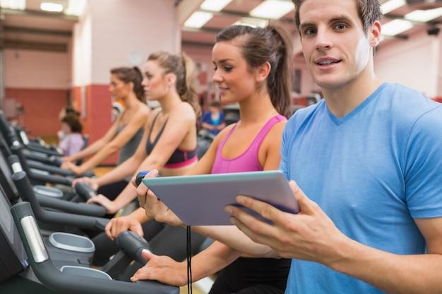 Męski gym instruktor z kobietami na karuzelach