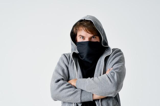 Męski haker w czarnej masce i kapturze na lekkiej kradzieży.