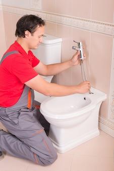 Męski hydraulik naprawia toaletę w mieszkaniu.
