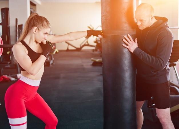 Męski instruktor szkoli młodą kobietę do wykonywania ręcznych uderzeń w worek treningowy na siłowni.