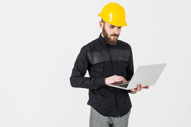 Męski inżynier jest ubranym hardhat używać laptop przeciw białemu tłu