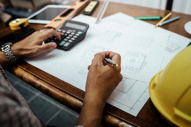 Męski inżynier pracuje z domu projektem i analiza architektonicznym planem na biurku.