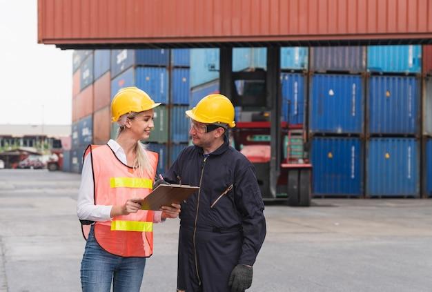 Męski inżyniera personelu logistycznego znak zatwierdza na dokumentach listy kontrolnej pudełek kontenery przy wysyłce ładunku ładunku