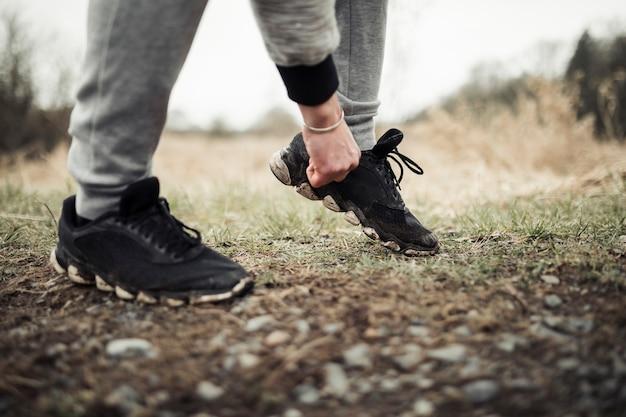 Męski jogger stoi na śladzie przystosowywa jego but