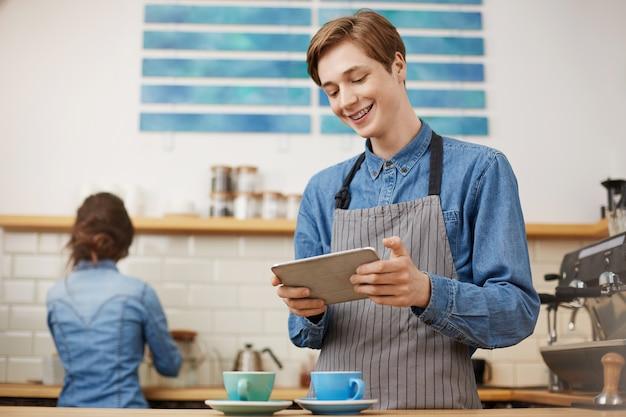 Męski kasjer bierze rozkazy używać zakładkę przy jaskrawym sklep z kawą.