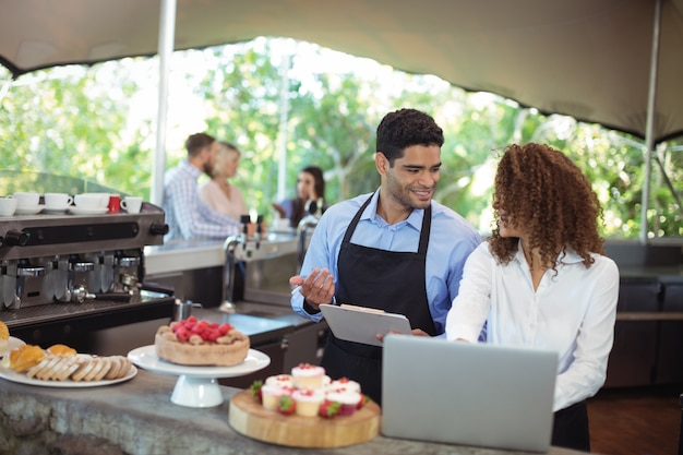Męski kelner i kobieta kelnerka z laptopa