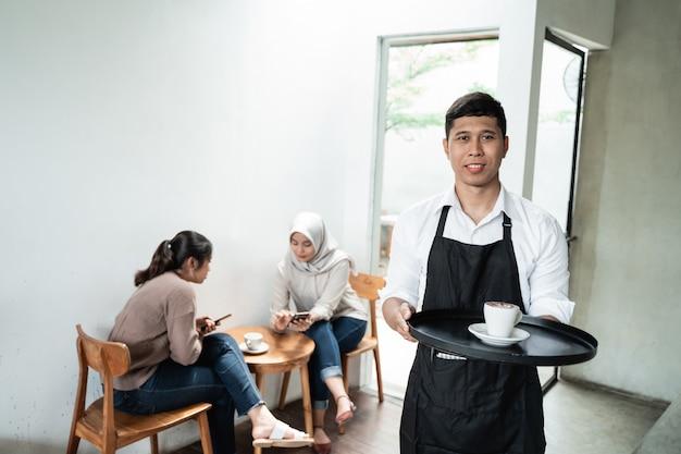 Męski kelner podaje filiżankę kawy
