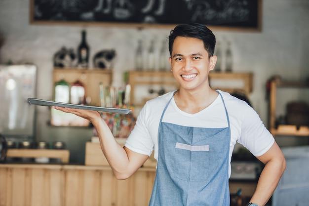 Męski kelner trzyma pustą tacę