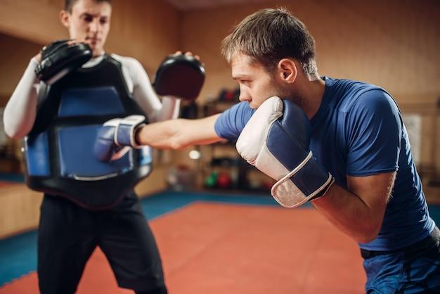 Męski kickboxer w rękawiczkach ćwiczy uderzenie ręką
