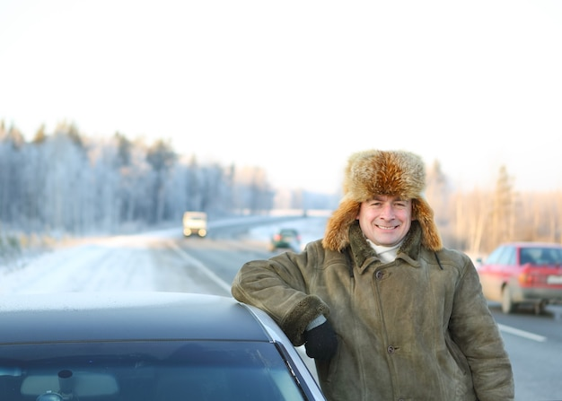 Męski kierowca samochodu na tle zimowego nieba