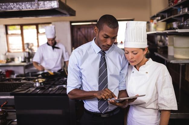 Męski kierownik i kobieta szef kuchni używa cyfrową pastylkę w kuchni