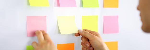 Męski kierownik przykleja małe notatki na ścianie