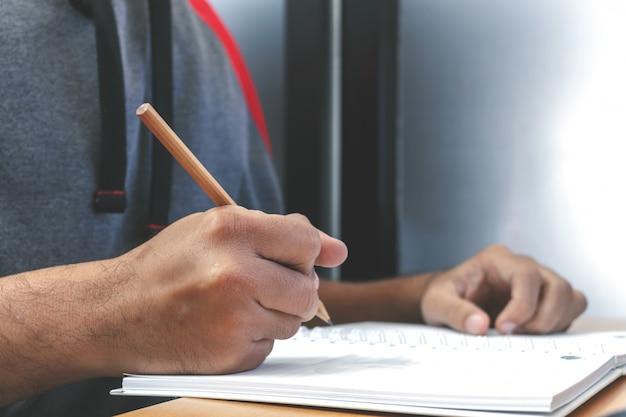 Męski kierownik stawia jego pomysły i pisze planie biznesowym przy miejscem pracy