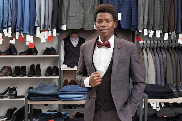 Męski klient jest ubranym w szarym kostiumu sklep, patrzeje kamerę.