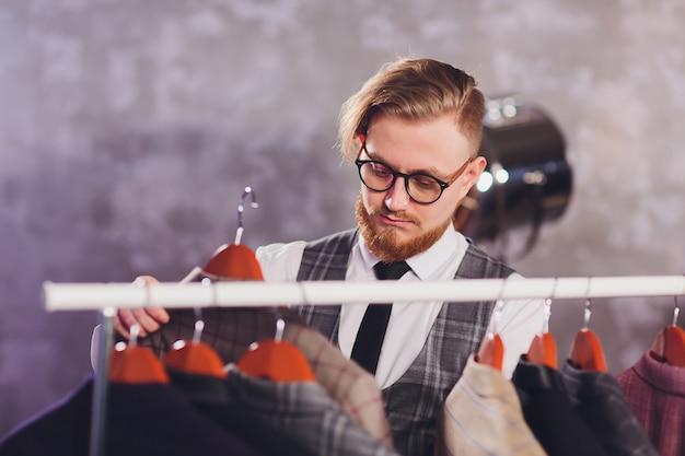 Męski klient szuka kurtki w mężczyzna ubrania sklepie.