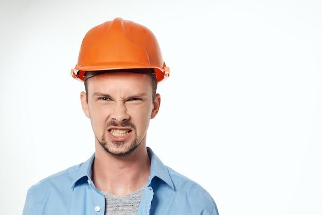 Męski konstruktor pomarańczowy kask inżyniera bezpieczeństwa w tle