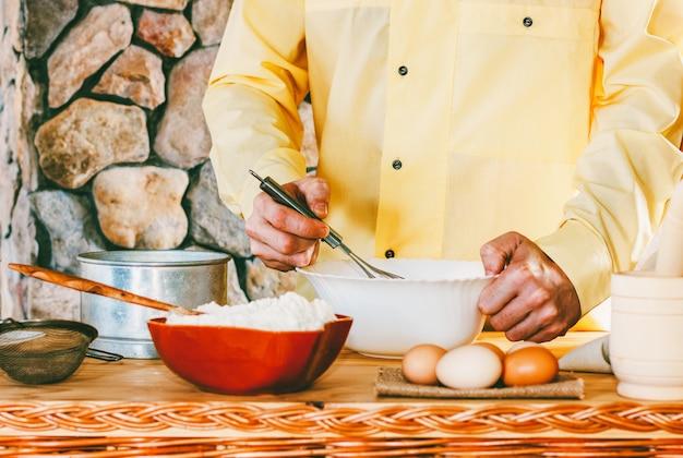 Męski kucharz w żółtej szacie ubij śmigać ciasto, selekcyjna ostrość