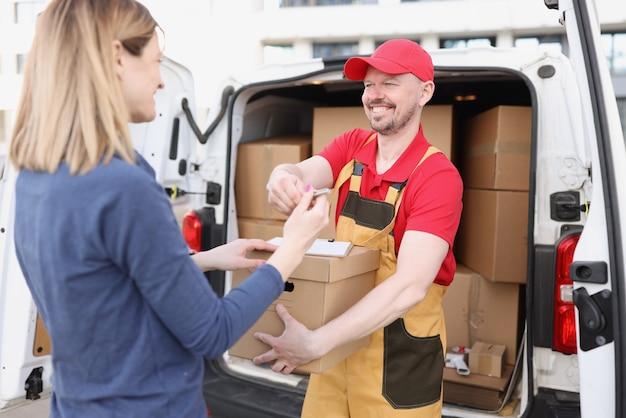 Męski kurier daje klientowi pokwitowanie, aby otrzymać paczkę!
