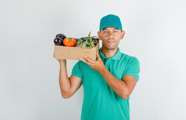 Męski kurier trzymający pudełko warzyw w zielonej koszulce z czapką i wyglądający wesoło