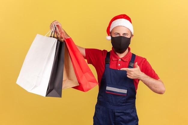 Męski kurier w masce i świątecznym kapeluszu świętego mikołaja wskazujący palcem na torby na zakupy