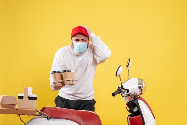 Męski kurier w masce trzymający kawę na żółto