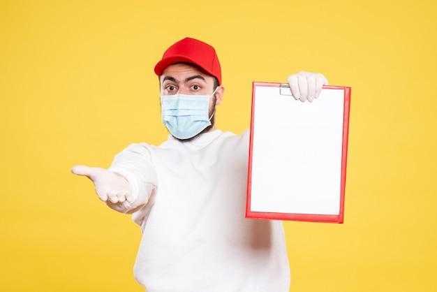 Męski kurier w masce trzymający notatkę do pliku na żółto