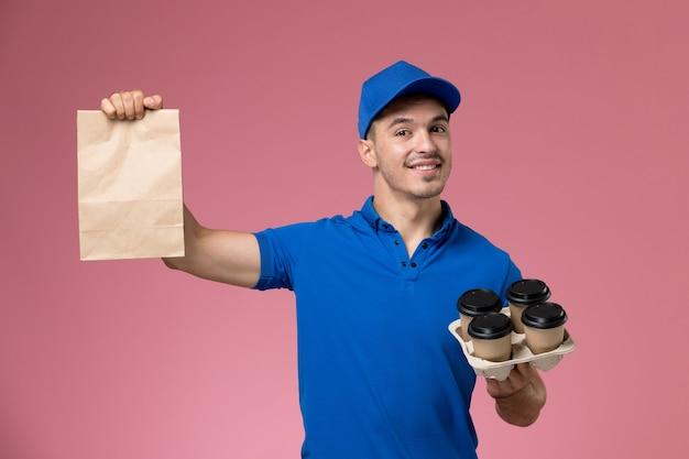 Męski kurier w niebieskim mundurze, trzymając dostawę pakiet żywności i kawę na różowym, jednolitym dostawie usług pracownika