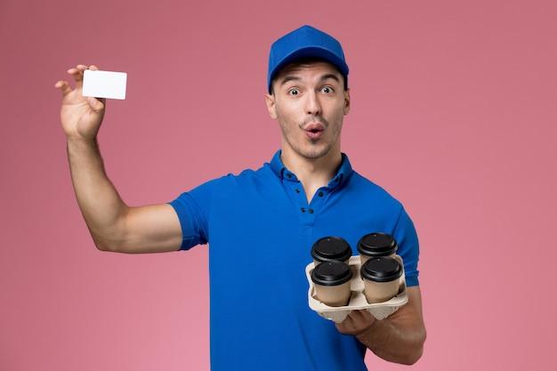 Męski kurier w niebieskim mundurze, trzymając dostawy filiżanek kawy i karty na różowym, jednolitym dostawie usług pracownika