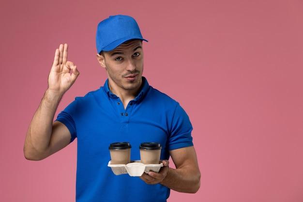 Męski kurier w niebieskim mundurze, trzymając filiżanki do kawy, pozowanie na różowym, jednolitym świadczeniu usług