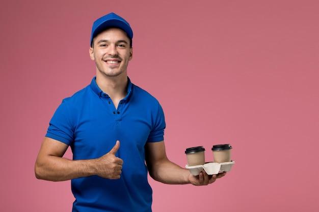 Męski kurier w niebieskim mundurze, trzymając filiżanki kawy dostawy i uśmiechając się na różowej, jednolitej dostawie usług pracownika