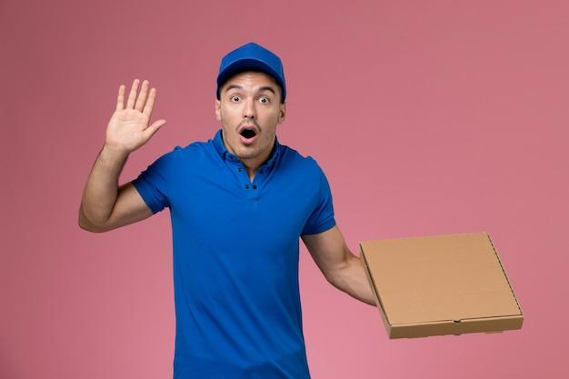 Męski kurier w niebieskim mundurze, trzymając pudełko dostawy żywności z zaskoczonym wyrazem na różowym, mundurze pracownika