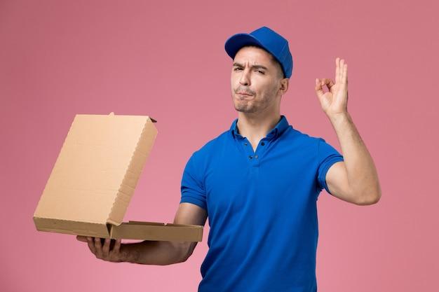 Męski kurier w niebieskim mundurze, trzymając pudełko z jedzeniem, otwierając je na różowej, jednolitej dostawie pracy usługowej