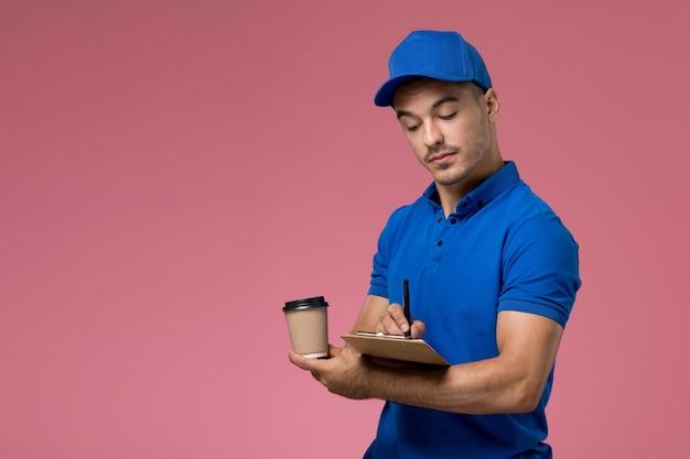 Męski kurier w niebieskim mundurze trzymający filiżankę kawy i zapisujący notatki na różowym, mundurze pracownika