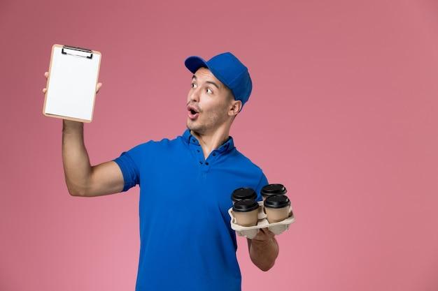 Męski kurier w niebieskim mundurze trzymający filiżanki do kawy i notatnik na różowej, jednolitej dostawie pracy serwisowej