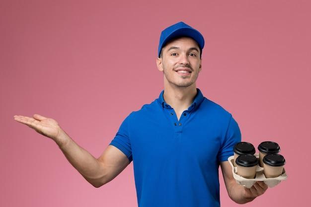 Męski kurier w niebieskim mundurze trzymający filiżanki z kawą z lekkim uśmiechem na różowym, jednolita dostawa usług pracownika