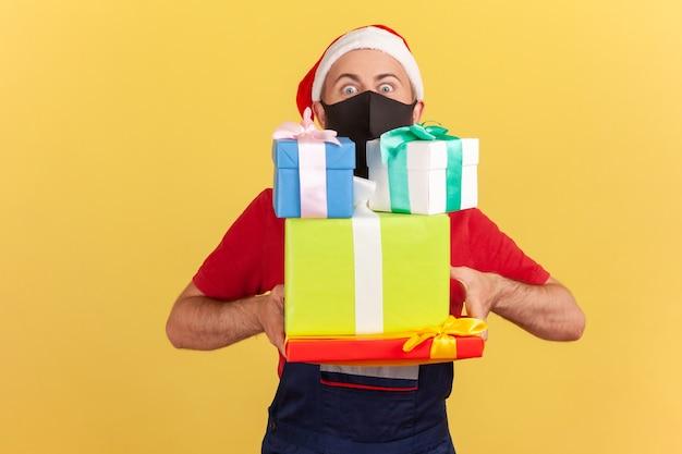 Męski kurier z ochronną czarną maską na twarzy dostarczający prezenty i prezenty