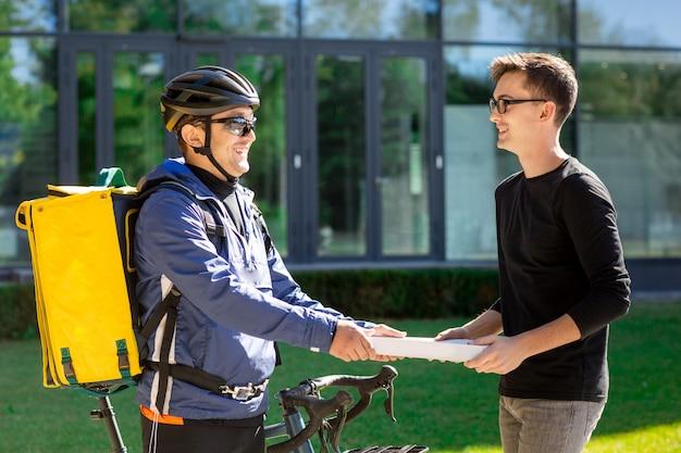 Męski kurier z rowerową i termiczną torbą daje pizzy boksuje klient na ulicie blisko biura