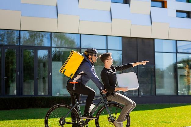 Męski kurier z termiczną torbą niesie faceta z pudełkiem na bagażniku rowerowym.