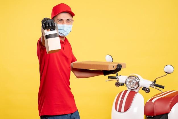 Męski kurier z widokiem z przodu z dostawą kawy i pudełkiem na żółtym mundurze motocyklowym w kolorze covid-virus