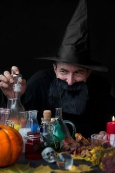 Męski mag alchemik warzy miksturę halloween święto