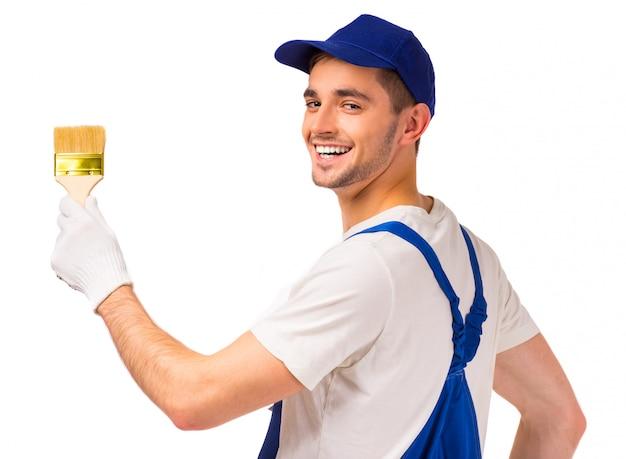 Męski malarz maluje ścianę i uśmiecha się.