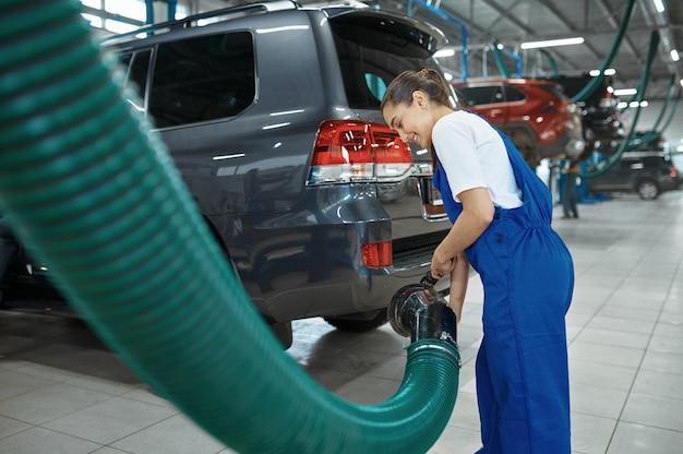 Męski mechanik przygotowuje się do przeglądu, serwisu samochodowego. garaż do naprawy pojazdów, mężczyzna w mundurze, wnętrze stacji samochodowej